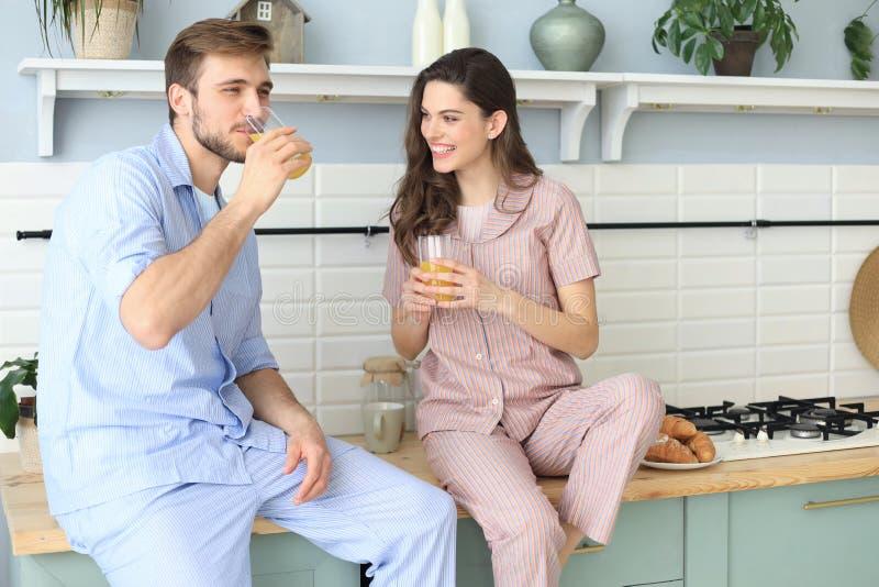 Portr?t von gl?cklichen jungen Paaren in den Pyjamas, die zusammen morgens in der K?che, trinkender Orangensaft zu Hause kochen stockfotos