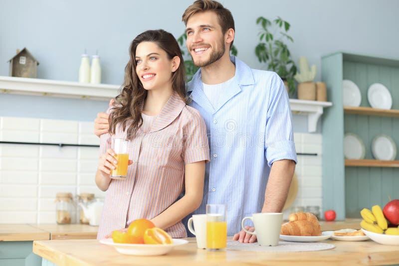 Portr?t von gl?cklichen jungen Paaren in den Pyjamas, die zusammen morgens in der K?che, trinkender Orangensaft zu Hause kochen lizenzfreies stockbild