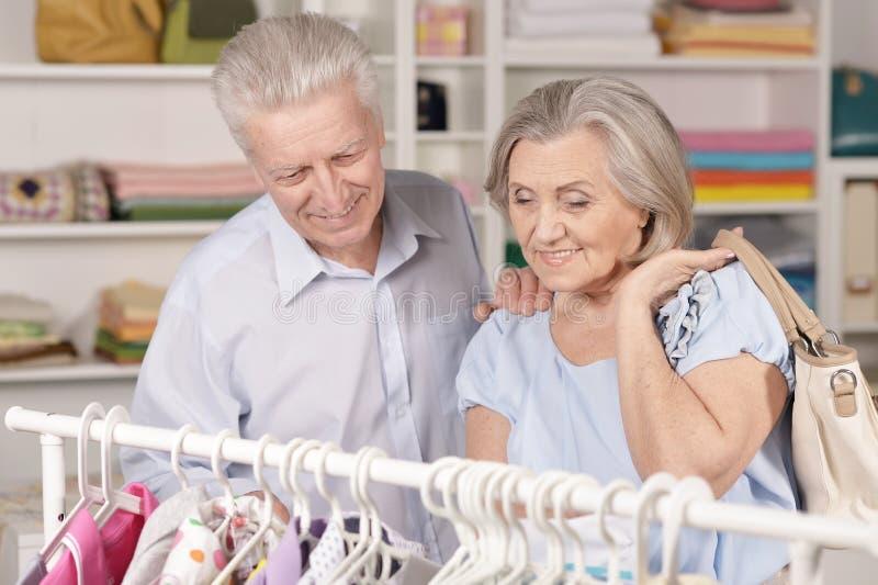 Portr?t von gl?cklichen ?lteren Paaren nahe Gestell mit Hemden lizenzfreie stockbilder