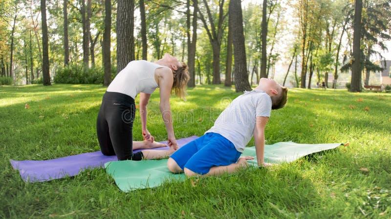 Portr?t von 12 Jahren alten Jungen, die Yoga?bung mit seiner Mutter am Park tun Familie, die am Wald meditiert und ausdehnt stockfotografie