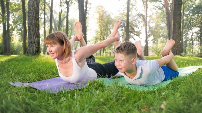Portr?t von 12 Jahren alten Jungen, die Yoga?bung mit seiner Mutter am Park tun Familie, die am Wald meditiert und ausdehnt stockbilder