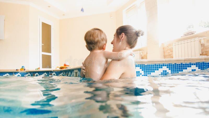 Portr?t von 3 Jahren alten Kleinkindjungen mit junger Mutterschwimmen im zuhause Pool Kind, das Schwimmen und das Handeln lernt lizenzfreies stockfoto