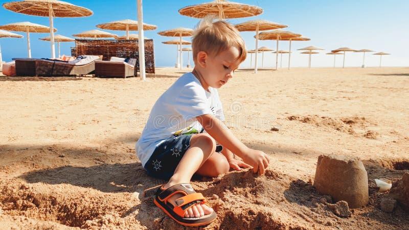 Portr?t von netten 3 Jahren alten Kleinkindjungen, die auf dem sandigen Strand sitzen und mit Spielwaren und errichtendem Sandbur stockbild