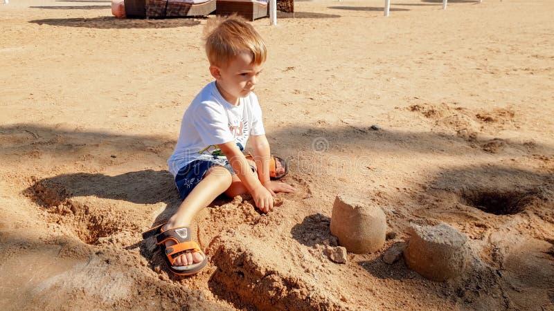 Portr?t von netten 3 Jahren alten Kleinkindjungen, die auf dem sandigen Strand sitzen und mit Spielwaren und errichtendem Sandbur lizenzfreies stockbild