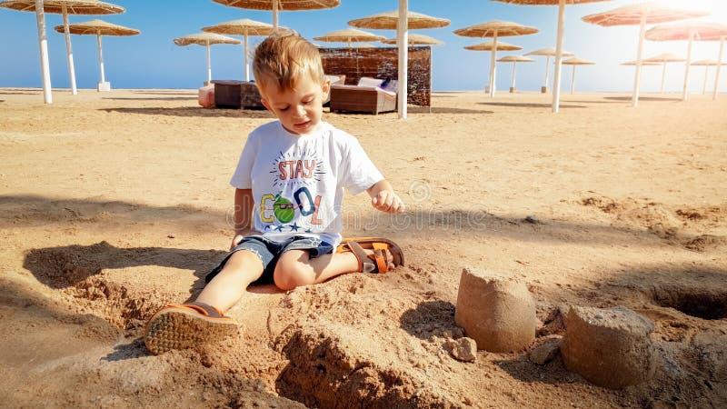 Portr?t von netten 3 Jahren alten Kleinkindjungen, die auf dem sandigen Strand sitzen und mit Spielwaren und errichtendem Sandbur stockbilder