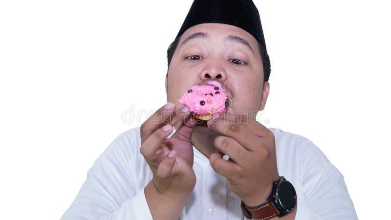 Portr?ts von asiatischen moslemischen M?nnern, die ?bergewicht sind, genie?en, Schaumgummiringe mit Vergn?gen zu essen lizenzfreies stockfoto