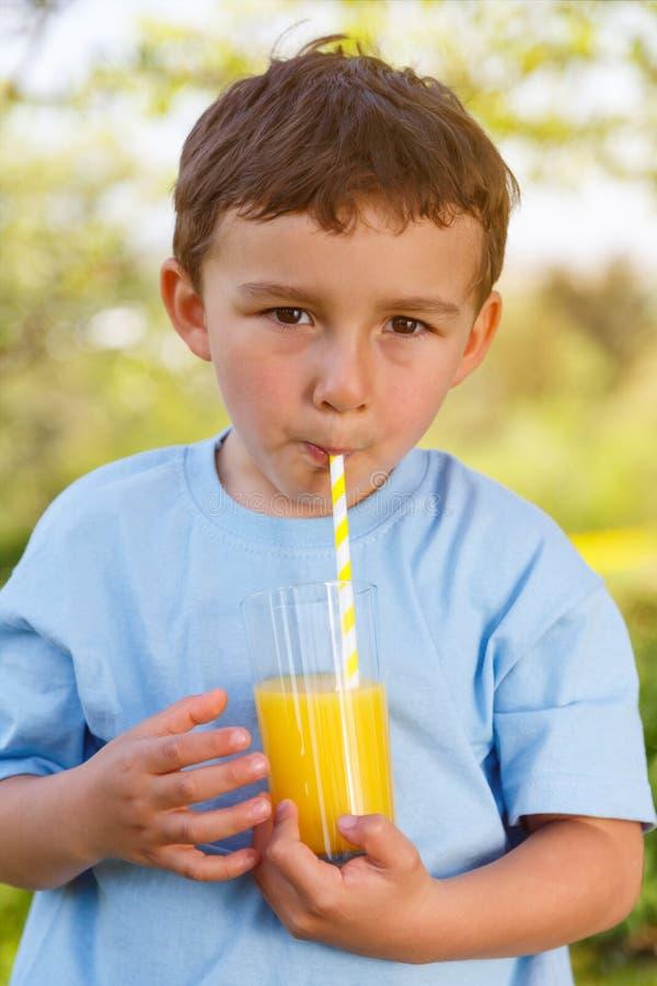 Portrai all'aperto bevente della bevanda del succo d'arancia del ragazzino del bambino del bambino fotografia stock libera da diritti