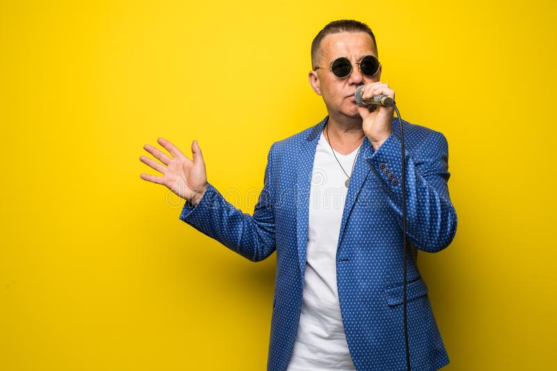 Portrai av den mogna mellersta åldermannen i dräkt som sjunger över mikrofonen som isoleras på gul bakgrund Sångarebegrepp arkivfoto