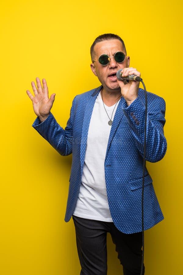Portrai av den mogna mellersta åldermannen i dräkt som sjunger över mikrofonen som isoleras på gul bakgrund Sångarebegrepp arkivbild