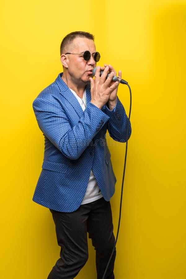 Portrai av den mogna mellersta åldermannen i dräkt som sjunger över mikrofonen som isoleras på gul bakgrund Sångarebegrepp royaltyfria foton