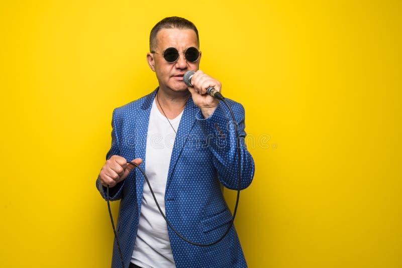 Portrai av den mogna mellersta åldermannen i dräkt som sjunger över mikrofonen som isoleras på gul bakgrund Sångarebegrepp arkivfoton