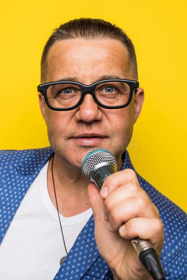 Portrai av den mogna mellersta åldermannen i dräkt som sjunger över mikrofonen som isoleras på gul bakgrund Sångarebegrepp arkivbilder