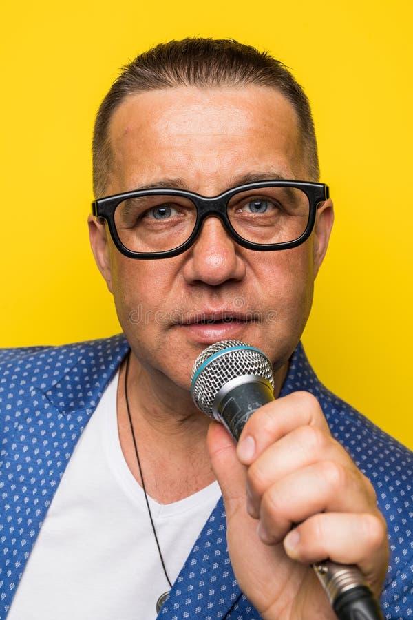 Portrai dell'uomo maturo di medio evo in vestito che canta sopra il microfono isolato su fondo giallo Concetto di Cantante fotografia stock