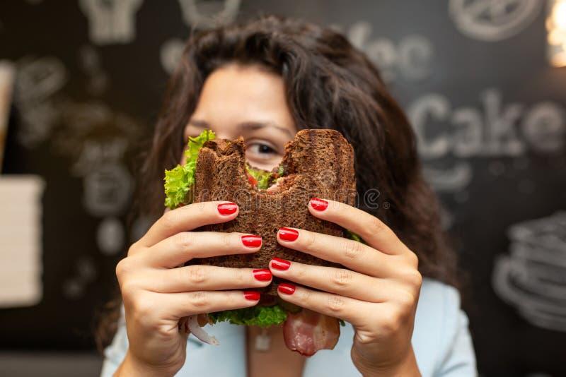 Portrai der jungen kaukasischen brunette Frau, die durch gebissenes Sandwich schaut stockbilder