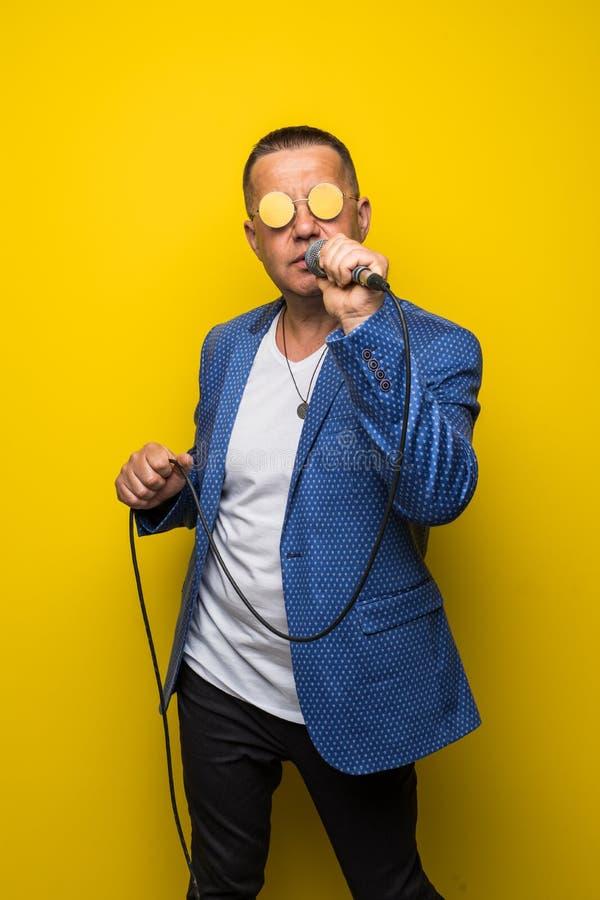 Portrai do homem maduro da Idade Média no terno que canta sobre o microfone isolado no fundo amarelo Conceito do cantor imagem de stock
