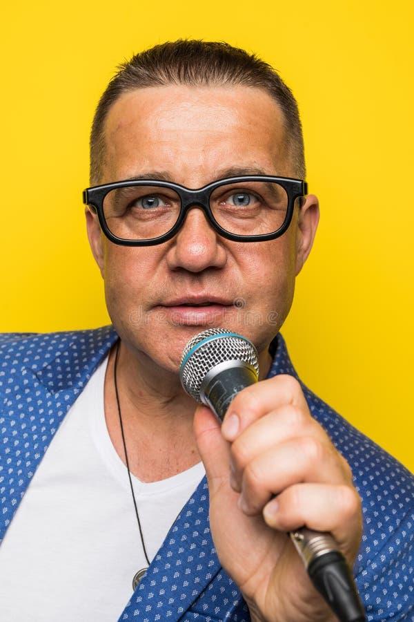 Portrai do homem maduro da Idade Média no terno que canta sobre o microfone isolado no fundo amarelo Conceito do cantor imagens de stock
