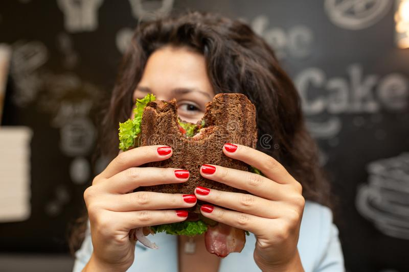 Portrai of young caucasian brunette woman looking through bitten sandwich stock images