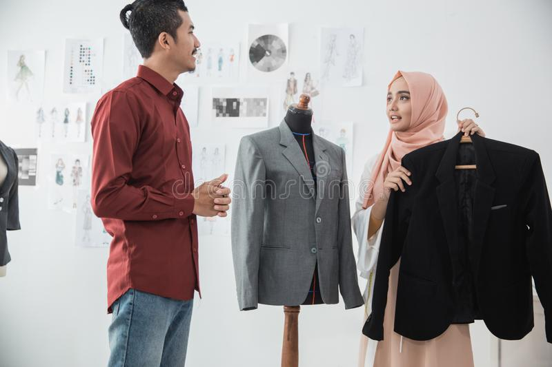 Male and female fashion designer discussing stock photo