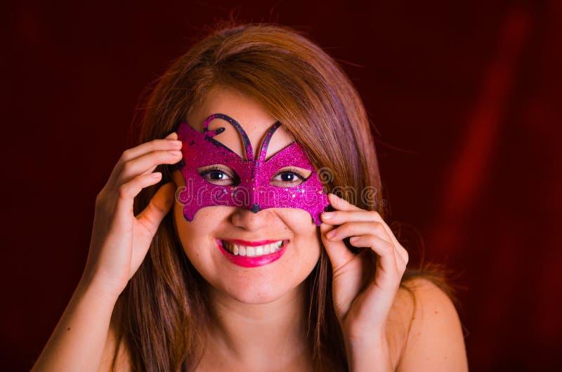 Portrain di bella donna di modello che indossa la maschera rosa di carnevale immagini stock libere da diritti