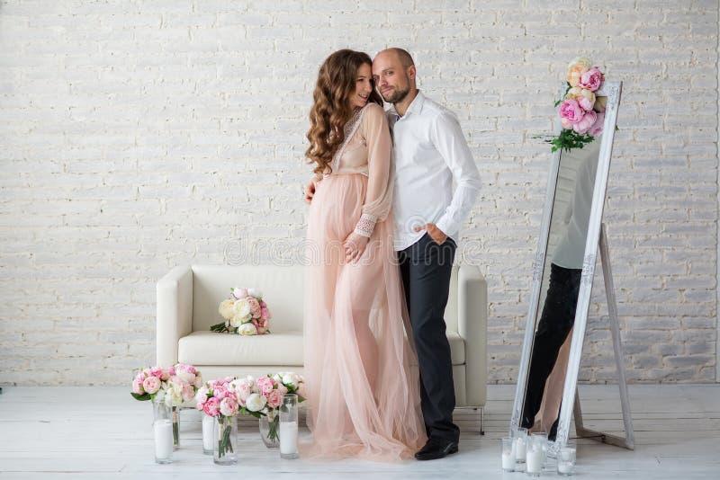 Portraint da mulher gravida e do seu marido no estúdio foto de stock royalty free