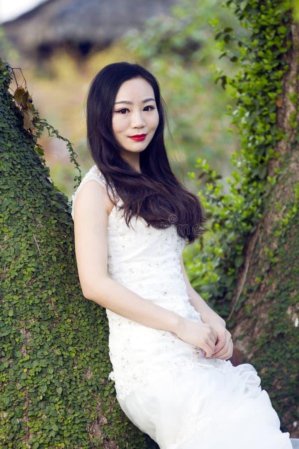 Portraint della sposa con il vestito da sposa bianco davanti ai vecchi alberi ed alla vecchia costruzione fotografie stock