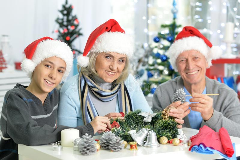 Portraint of grandparents with boy preparing for Christmas. Happy grandparents with their teen grandson preparing for Christmas at home stock photography