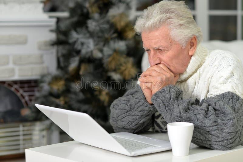 Portraint starszy mężczyzna z laptopem w domu obrazy stock