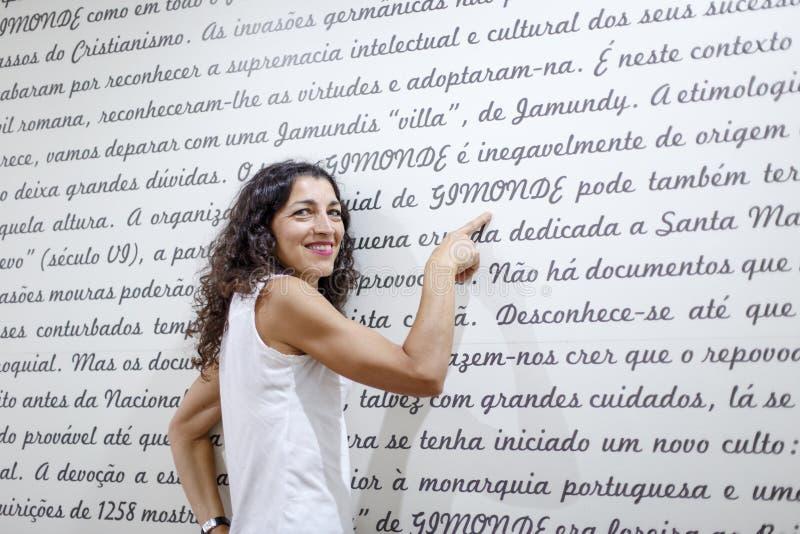 Portrair av den härliga unga kvinnan som pekar ett finger på ordet Gimonde fotografering för bildbyråer