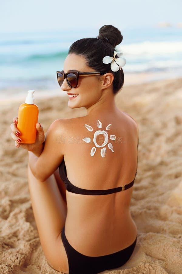 Portrair de belle crème de application femelle de crème de Sun sur l'épaule bronzée Protection de Sun images libres de droits