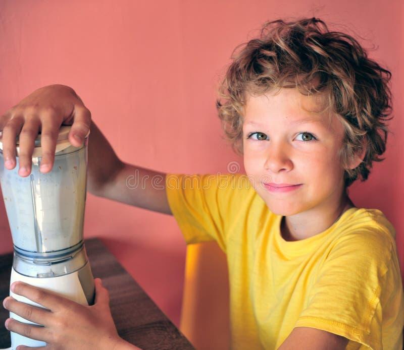Portrair di un ragazzo felice che produce frappè per se stesso fotografia stock