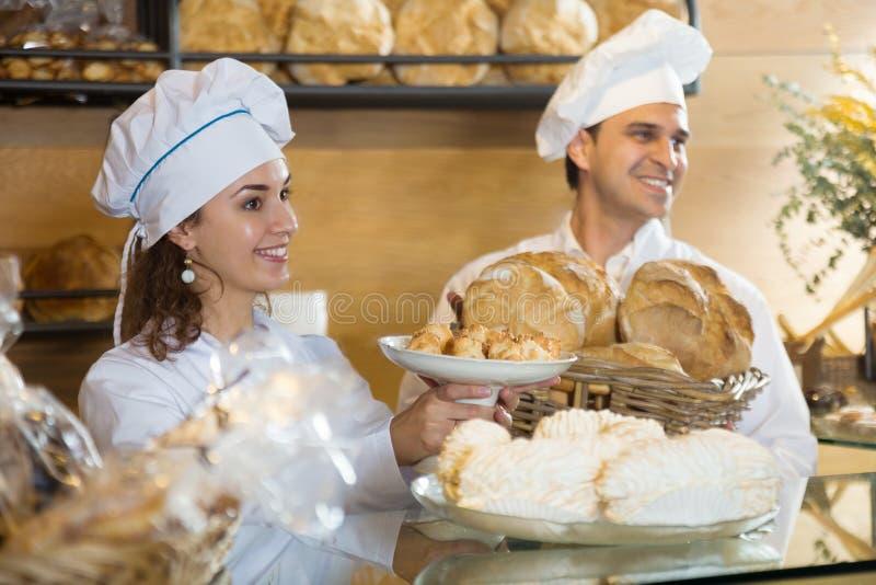 Portrair van het glimlachen twee chef-kokgebakje in het Italiaans bakkerij royalty-vrije stock foto