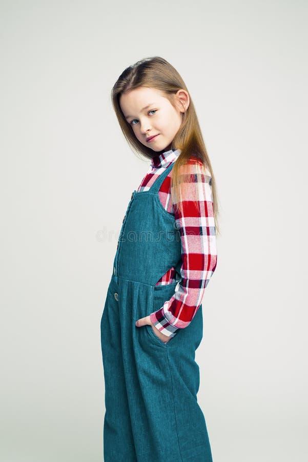 Portrait ? la mode d'une petite fille dans une salopette de denim et une chemise de plaid tir du studio des enfants photos stock
