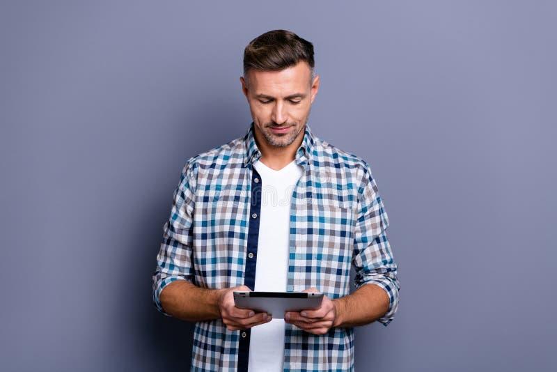 Portrait à lui il contenu attrayant gentil a focalisé le type aux cheveux gris barbu portant le Web vérifié de lecture rapide de  image stock