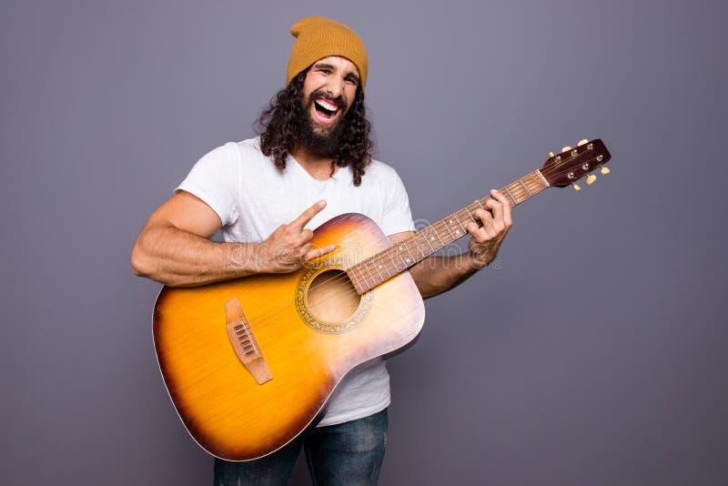Portrait à lui il gentil type aux cheveux ondulés gai gai attirant beau fou frais jouant le bruit frappé populaire de guitare image stock