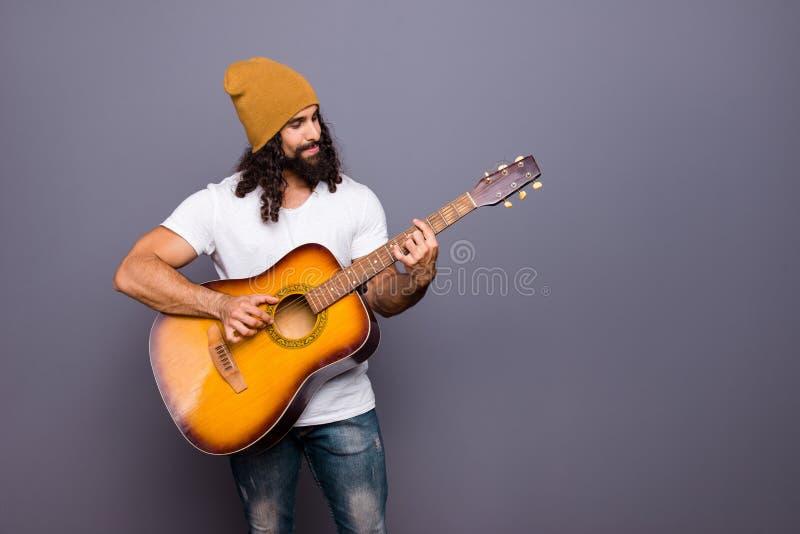 Portrait à lui il gentil type aux cheveux ondulés sûr gai attirant beau jouant la guitare a frappé la composition en roche de bru images libres de droits