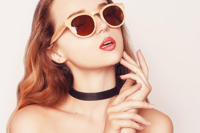 Portrait élégant d'une fille de modèle de beauté utilisant les lunettes de soleil en bois foncées Femme de mode de plan rapproché photos libres de droits