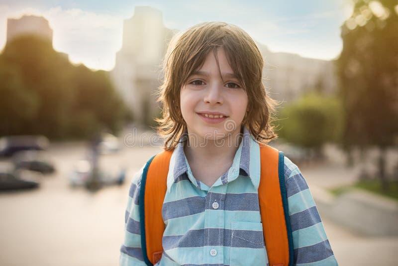 Portrait émotif d'un écolier de sourire avec une sacoche sur le sien image stock