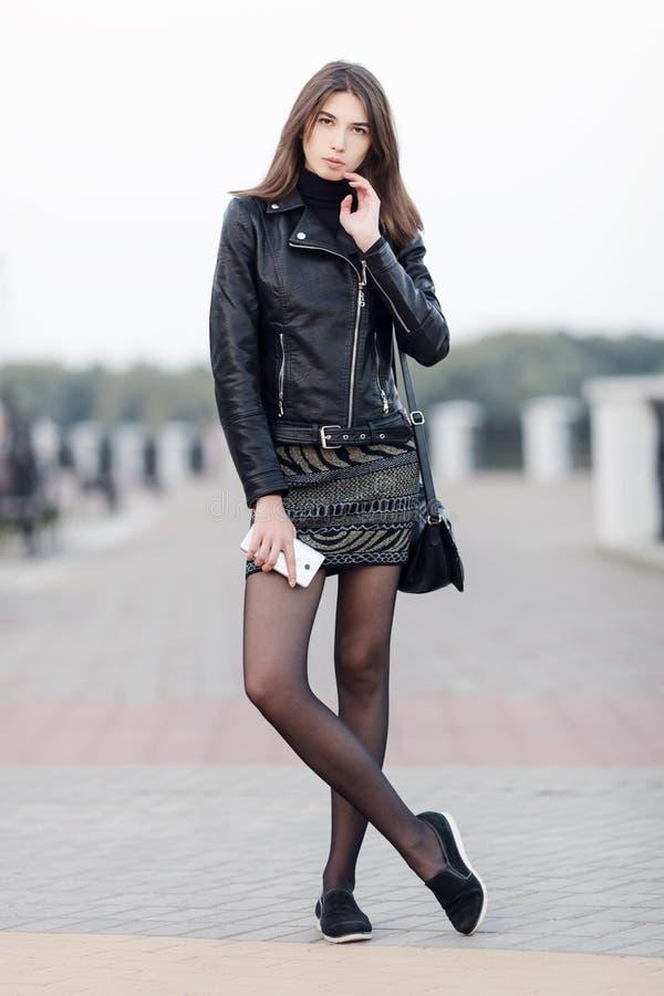 Portrait émotif d'une jeune jolie femme de brune posant le parc intégral de ville d'extérieur portant le manteau en cuir noir jug photo libre de droits