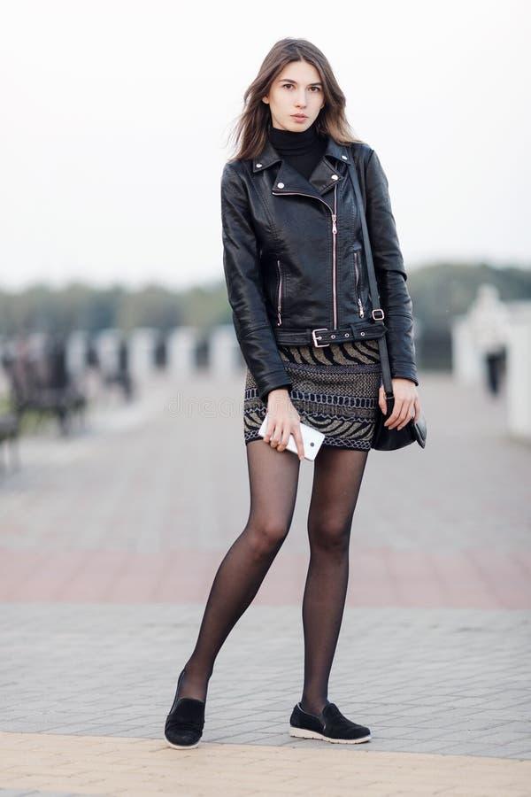 Portrait émotif d'une jeune jolie femme de brune posant le parc intégral de ville d'extérieur portant le manteau en cuir noir jug image libre de droits