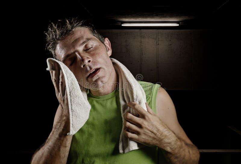 Portrait énervé foncé de jeune homme fatigué et épuisé en sueur de sport avec la bouteille d'eau refroidissant après séance d'ent image stock