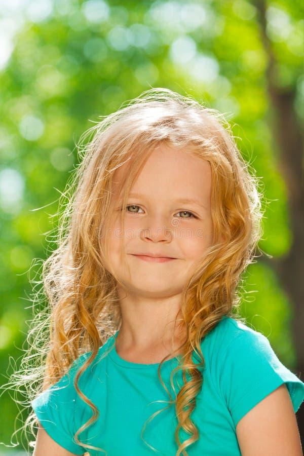Portrait étroit de petite fille heureuse bouclée dehors image libre de droits
