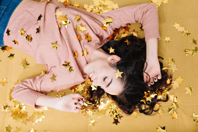 Portrait from above cheerful pretty young woman with curly brunette hair laying on beige couch in golden tinsels stock image