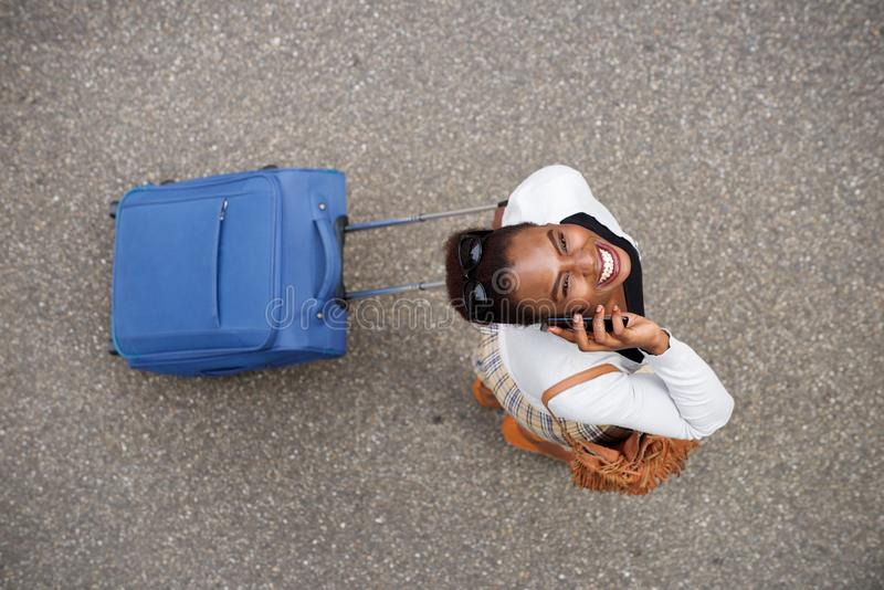 Above of happy african american woman walking with travel bag and mobile phone. Portrait from above of happy african american woman walking with travel bag and royalty free stock photography