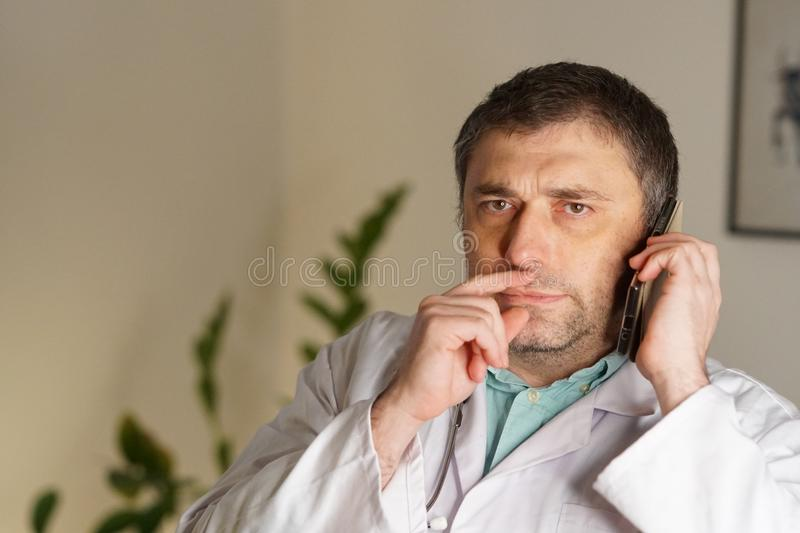 Portrait of absorbed doctor talking on his mobile phone stock images