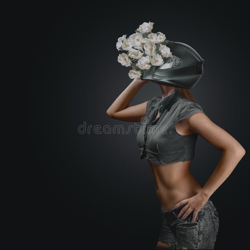 Portrait abstrait de mode de jeune femme dans le casque de moto avec des fleurs photographie stock libre de droits