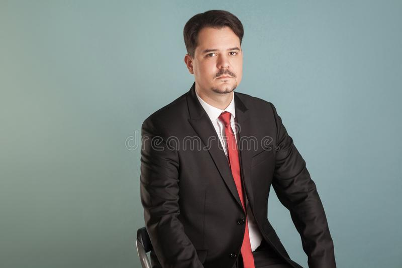 Portrait of acting shoot sitting businessman lookking seriously royalty free stock photo