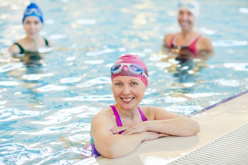 Smiling Mature Woman Posing in Pool stock image