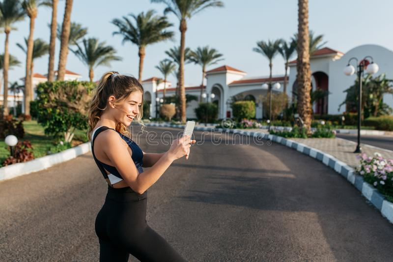 Portrait active happy sportswoman making selfie on street in tropical city. Sunny morning, cheerful mood, motivation royalty free stock photography
