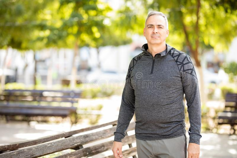 Active mature man before exercise in the city. Portrait of active mature man standing outdoors in the park before doing some exercise royalty free stock photo