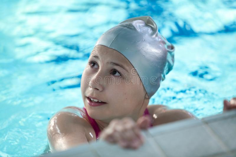 Portrait of adolescent girl standing in water of swimming pool with rubber cap. Portrait of adolescent girl stands in water of swimming pool with rubber cap royalty free stock image